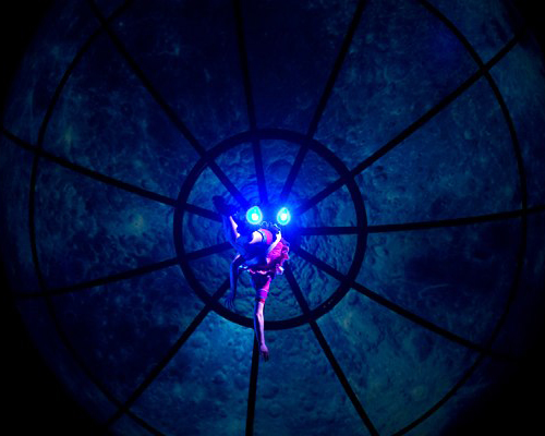 An acrobat performing under the giant video sphere.