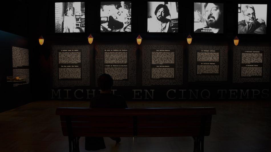 Assis sur un banc de parc, un spectateur regarde l'installation vidéo «Michel en 5 temps».